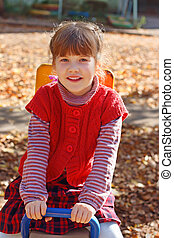 Little smiling girl sits on wooden seesaw on playground at sunny day