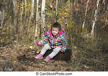 Little smiling girl sitting on a tree stump in autumn forest.
