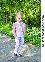 Little smiling girl walkink in the park