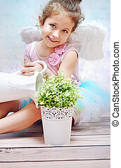 Little smiling girl watering plant