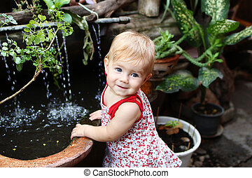 Little smiling girl with blond hair and blue eyes in sundress is standing in garden with pot plants and waterfall.