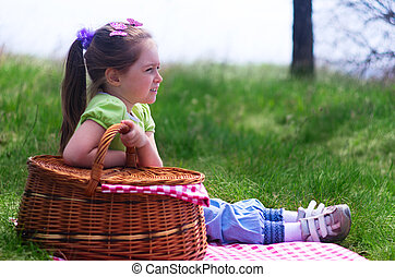 Little smiling girl with picnic basket
