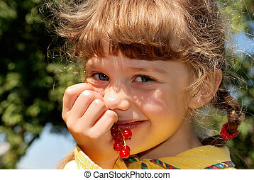 little smiling girl with red currants outdoor