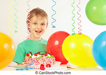 Little smiling kid with birthday cake and balloons