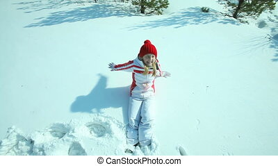 Little snow angel - Teenage girl falling in the snow and...