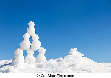 little snowmen figures building a pyramide in the snow