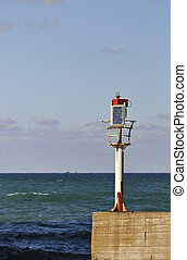 Little solar lighthouse on a concrete jetty with sea and sky in the background