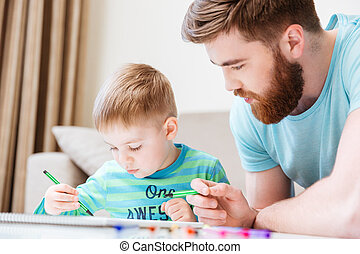Little son and his father drawing with markers together