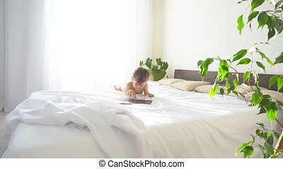little son lies on the bed in the bedroom and looks at...