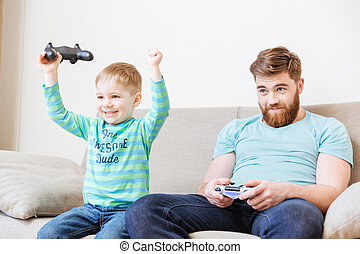Little son playing computer games with father and winning