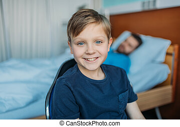 little son sitting on chair near his sick father sleeping on hospital bed at ward, dad and son