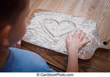 little son wrote by finger on a plaque with flour the word mom