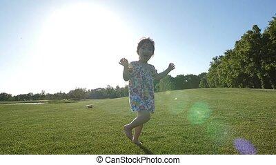 Little special needs girl running on grass in park - Cute...