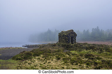 little stone hut covered by moss at the shallow banks of ...