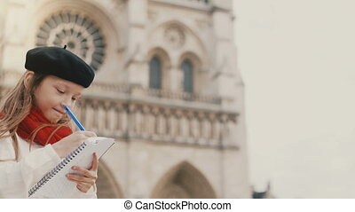 Little stylish girl in beret drawing the picture in notebook...