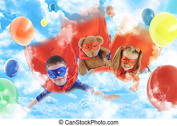 Two young superhero children are flying in the sky with balloons and a teddy bear for a party or rescue concept.