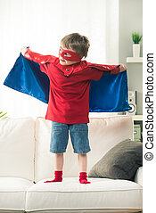 Superhero boy standing on sofa with arms raised showing his superpowers.