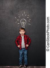 Little surprised boy having idea over chalkboard background with drawings