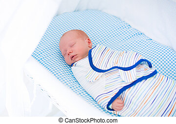 Little swaddled baby in white bed