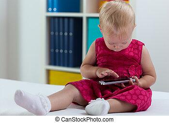 Little sweet girl interested in smart phone