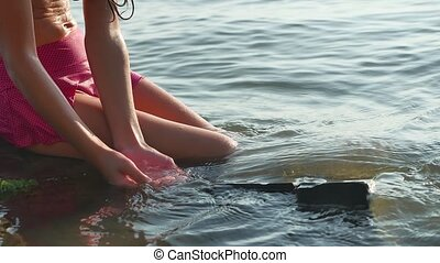 little teen girl is sitting in the sea in the water and...
