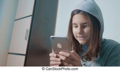 little teen hood girl writes a message chatting in social...
