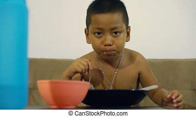 Little Thai boy eating rice
