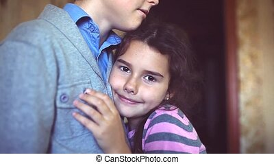 little the girl clung to the boy's chest. girl and boy...