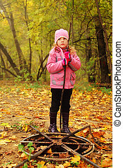little thoughtful girl in autumn park stand near old rusty...