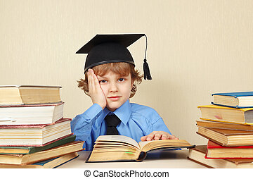 Little tired boy in academic hat studies old books - Little...