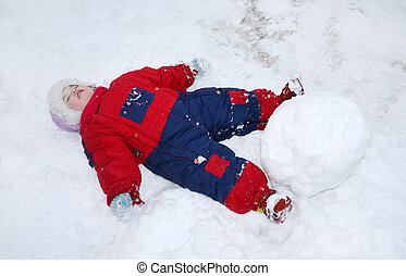 Little tired girl wearing warm jumpsuit lies on snow