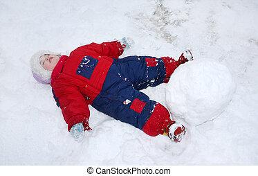 Little tired girl wearing warm jumpsuit lies on snow near ...