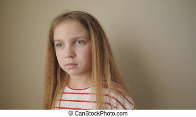 Little tired girl with long blonde hair posing to camera and swinging her body from side to side at room. Portrait of small bored child against the background of beige wall. Close up Slow motion.