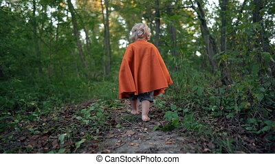 Little toddler boy cosplay gnome or hobbit in long cape walking barefoot in green forest. Halloween, kids concept. Amazing fairy tale character. Slow motion. . High quality FullHD footage