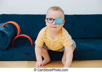Little toddler boy in lazy eye patch is playing with toy cars