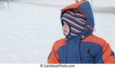 Little toddler boy play in the winter playground and having fun with snow. Winter lifestyle concept.