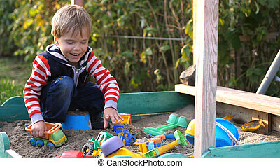 Little toddler boy playing in sandbox on playground in sunny day