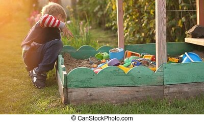 Little toddler boy playing in sandbox on playground in sunny...