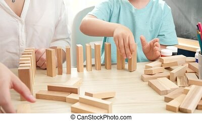 Little toddler boy putting wooden blocks or domino in long line. Concept of children education at home during lockdown and staying at home.Parents playing with children.