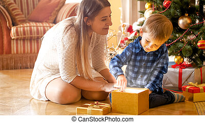 Little toddler boy sitting with mother under Christmas tree and opens magical glowing gift box