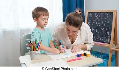 Little toddler boy with young mother drawing and painting with colorful pencils. Doing homework and edcucation with parents