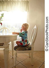 Little Toddler Child Sitting at Dinner Table on Sunny Morning Eating Breakfast Cereal
