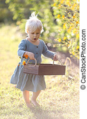 Little Toddler Child Walking Through the Garden Picking Flowers on Summer Day