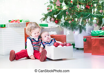 Little toddler girl and her newborn brother helping to decorate
