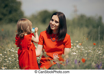 Mom helping little child to stay hydrated during play time