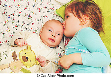 Little toddler girl kissing her baby brother, kids playing together