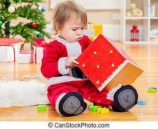 Little toddler girl opening a big present box