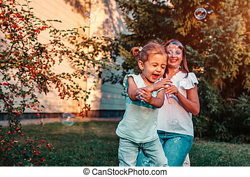 Little toddler girl playing with soap bubbles her mother blows in summer park. Happy kid having fun outdoors