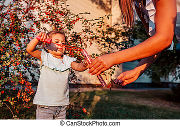 Little toddler girl playing with soap bubbles in summer park. Happy kid having fun outdoors. Mother helping daughter