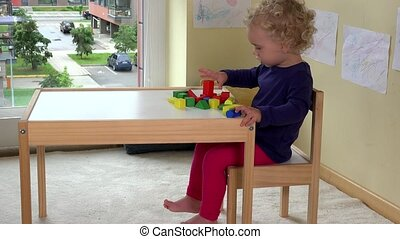 Little toddler girl playing with wooden bricks toys near table at home